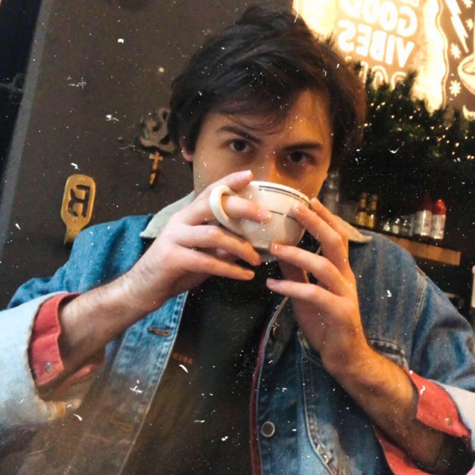"""Noah sips coffee and looks directly into the lens"""